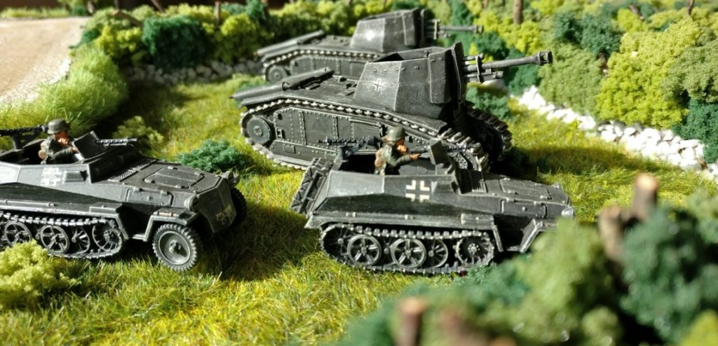 Zwei Sd.Kfz.250/1 der Panzer-Aufklärungs-Abteilung 26 ziehen an den 105 mm leFH 18/3 auf Gw B-2 740(f) vorbei.