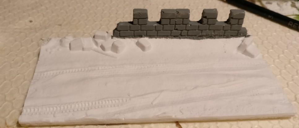 """Die Squad-Base """"Winter"""" Radfahrzeugspuren im Schnee vor Ruine."""
