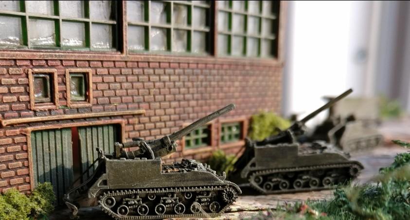 Abgeschlossener Bau von Industriehallen: aus dieser Perspektive wirken die Gun Motor Carriage besonders mächtig.