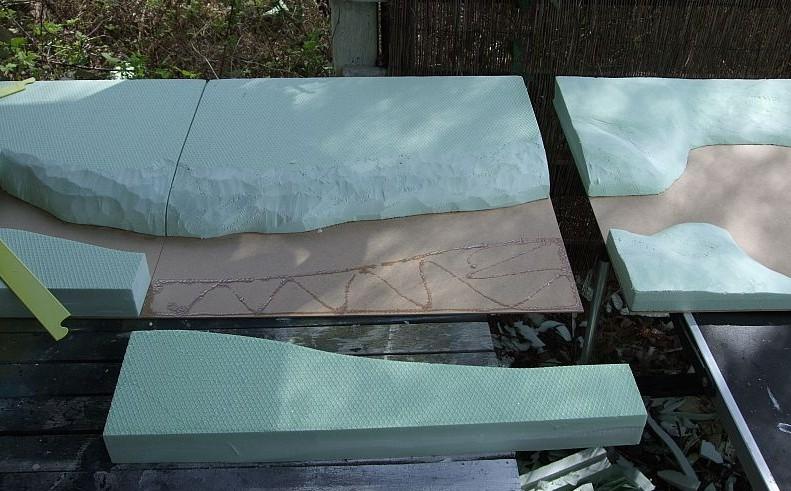 Hier werden die Komponenten  Kanalmauer und natürliches Gegenufer auf die Trägerplatten (Holz/MDF-Platten) aufgeklebt.