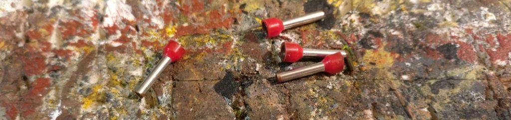Hier die verkürzten Aderendhülsen. Der rote Schaft wurde bereits mit dickflüssiger Farbe verfüllt und getrocknet. Der rote Schaft sowie die metallene Klemmhülse werden nicht bemalt.