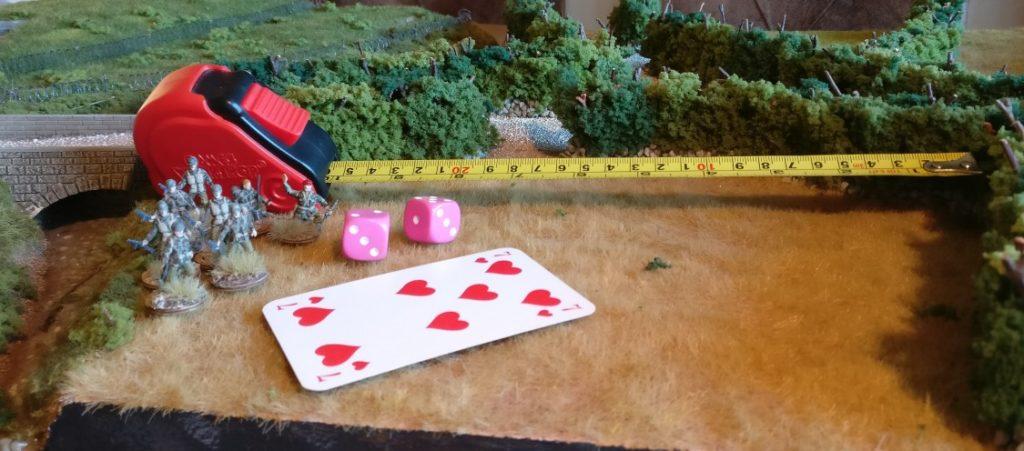 """Dieser Trupp bewegt sich NICHT in schwerem Gelände. Sein Befehlstest führte mit den beiden Würfeln ( eine rote Karte erlaubt zwei W6-Würfel für einen Befehlstest auf Bewegung ) ebenfalls zu dem Ergebnis von """"7"""" Augen. In diesem Fall wird auf den Kartenwert von """"7"""" nichts addiert, denn es liegt ja kein schweres Gelände vor dem Trupp in Bewegungsrichtung. Somit ist der Befehlstest gelungen, denn der Kartenwert von """"7"""" wurde erwürfelt. Der Infanterietrupp darf sich nun um bis zu 10 Zoll bewegen. Das Maßband zeigt die Bewegungsweite von 10 Zoll an."""