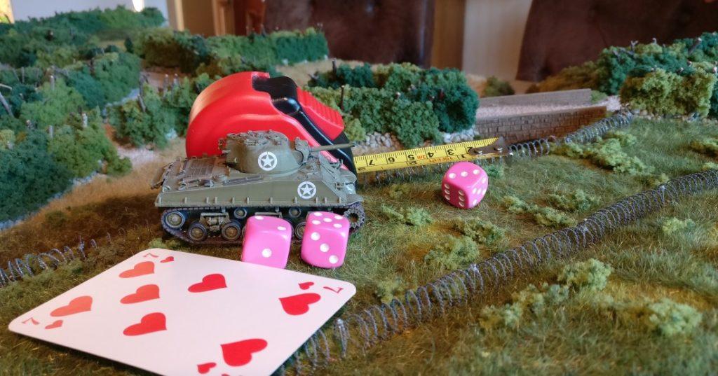 """Die rote Kommandokarte erlaubt zwei W6-Würfel für den Befehlstest. Hier haben die beiden W6-Würfel insgesamt """"7"""" Augen erwürfelt. Die Kommandokarte besitzt den Kartenwert """"7"""". Auf den Kartenwert wird für die bevorstehende Bewegung durch schweres Gelände einmal """"+2"""" addiert. Somit müsste der Wurf des Befehlstests mindestens """"9"""" Augen ergeben. Dies geschah nicht. Daher wird der Panzer langsamer fahren. Der rechts sichtbare W6-Würfel wurde benutzt, die Bewegungsweite zu erwürfeln. Die erwürfelten """"3"""" Augen ergeben eine Bewegungsweite von 3 Zoll, die durch das Maßband angezeigt wird."""