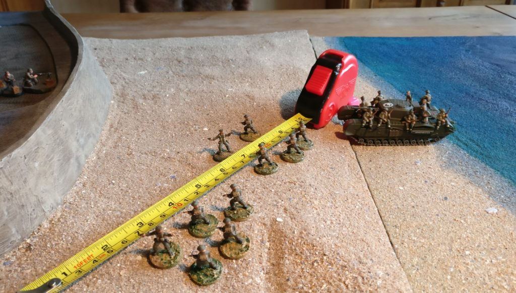 Auf diesem Bild erkennt man, die Tank Riders auf dem Churchill. Die Tank Riders können einfach absitzen und direkt ins Gefecht gehen. Einzige Bedingung: das Absitzen muss im Radius von 10 Zoll um den Churchill geschehen. Auf dem Bild ist dies der Fall. Zwei 5-Mann-Trupps gehen die Strandmauer an.