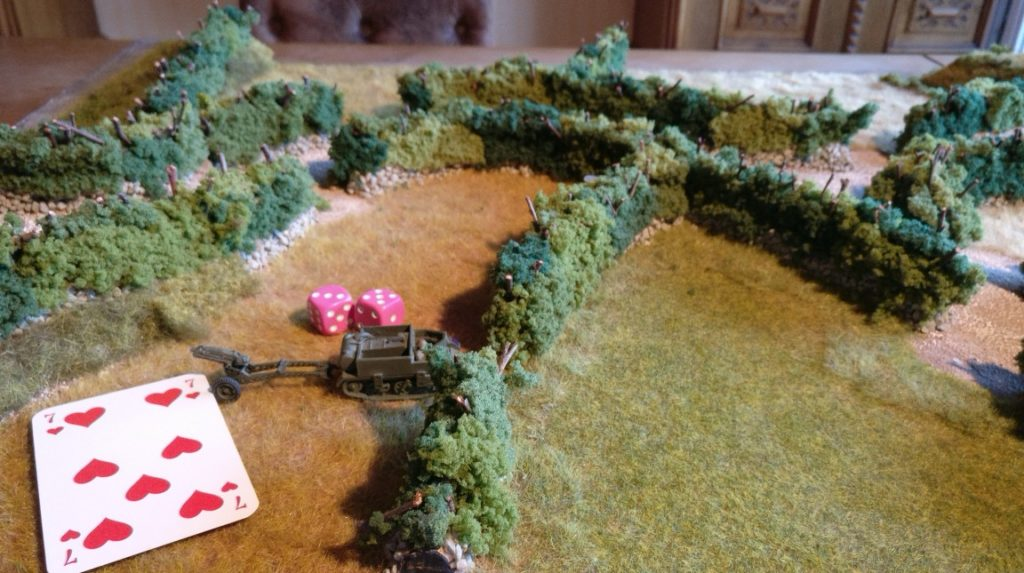 """Dieses Gun Team möchte auf der rechts gelegenen Wiese in Stellung gehen. Der Bren Carrier hat für seine Rote Kommandokarte erfolgreich mit den beiden W6-Würfeln die erforderliche Augenzahl von """"7"""" erwürfelt. Er darf mit angehängtem Geschütz auf die Wiese fahren."""