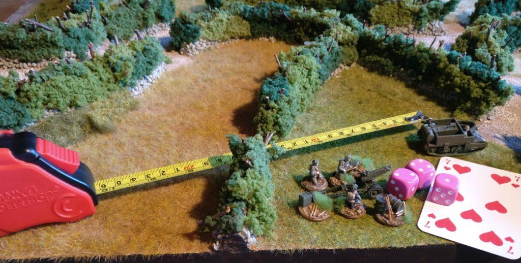 Während der Fahrt wurde das Geschütz abgekuppelt. Der Bren Carrier fährt noch ein Stück weiter. Das Geschütz geht in Stellung und das Gun Team feuert den ersten Schuss ab. Hierzu wurden für den Schuss drei W6-Würfel auf den Wert der selben Roten Kommandokarte gewürfelt, die auch schon für die Bewegung genutzt wurde.