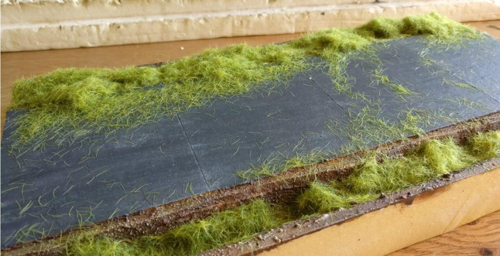 Das Gras wird in zwei Längen aufgetragen. Ganz unten im Graben kommt 6,5mm-Gras, weiter oben kürzereres 2,5mm-Gras zum Einsatz.
