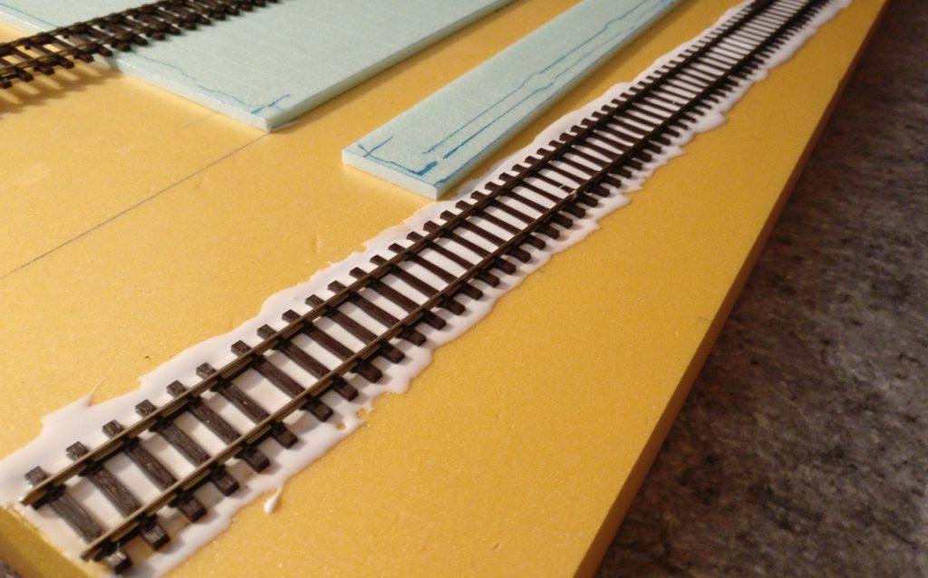 Das Gleisbett des geschwungen verlaufenden Rangiergleises neben der Fabrikhalle ist gesuppt. Das Gleis wurde vorsichtig hineingleiten gelassen.