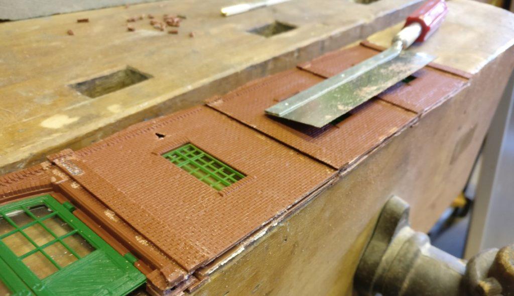 Im Generalunternehmen Industriebau wird auch gesägt. Die unten überstehenden Mauervorsprünge aus der grauen Lokschuppenvergangenheit der Mauersegmente müssen beseitigt werden.