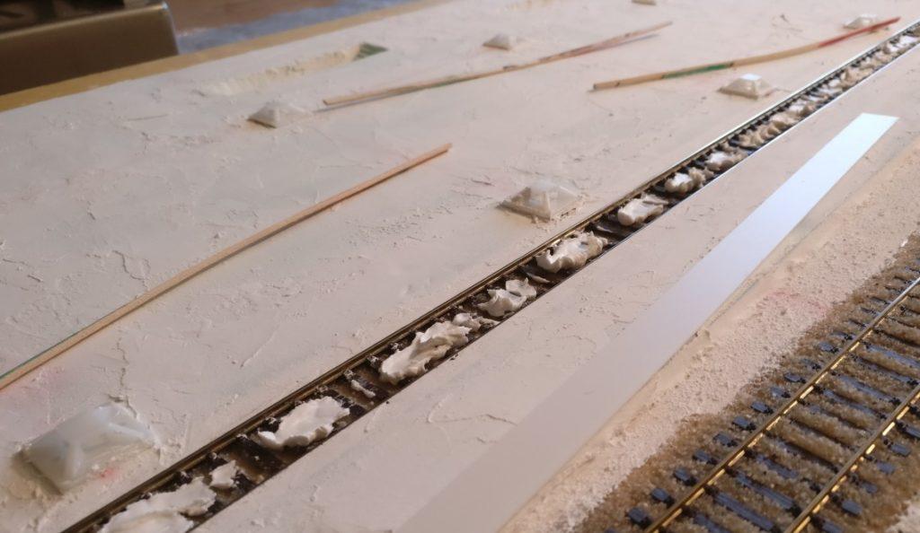 Der Streifen Plastic Sheet wird mittels Innenspachtel auf dem  Gleiskörper befestigt.