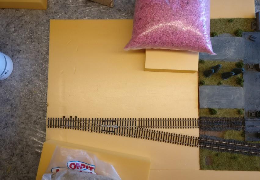 Viel ist es ja nicht. Gerade mal zwei Gleistücke werden an die Weiche angelegt. Die wurden zuvor natürlich an der Plattenkante passend mit der Säge abgelängt. Jetzt wird nur noch fluchtend ausgelegt.  Die unterliegende Spielplatte wird mittels anderer Plattenstücke in der passenden Stellung an der großen Hallenplatte gehalten.