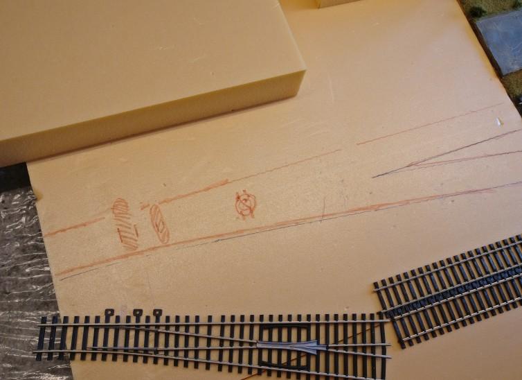 Hier sind die Konturen der Gleiskörper mit rotem Filzstift markiert. Es ist der Rahmen für die mit PONAL einzusuppende Fläche. Denn: Neben dem Aufbringen der Geleise steht auch das Einschottern mit Quarzsand an. Da hat der PONAL zwei Aufgaben zu meistern.