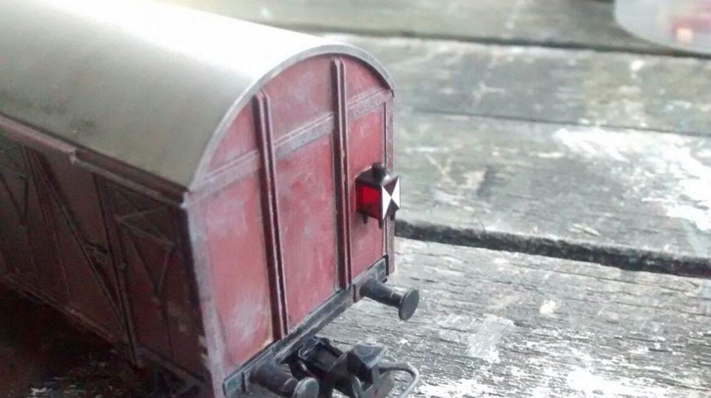 Das gesuperte Zugschlusslicht an dem einen gedeckten Güterwagen.