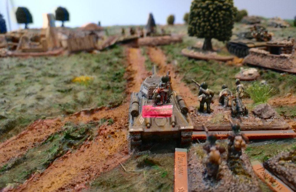 Der T-34/76 mit begleitender Infanterie auf dem Vormarsch auf das von den deutschen Truppen eingenommene Gehöft.