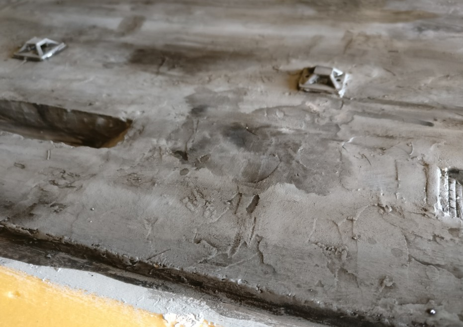 Die dünne schwarze Lasur arbeitet die feinen Strukturen aus der  Bodenplatte heraus.