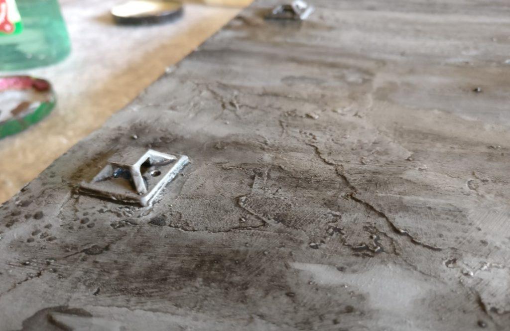 Eine weitere Schicht aufgetupfte schwarze Lasur  bringt ölige Schmutzspuren auf den Beddong.