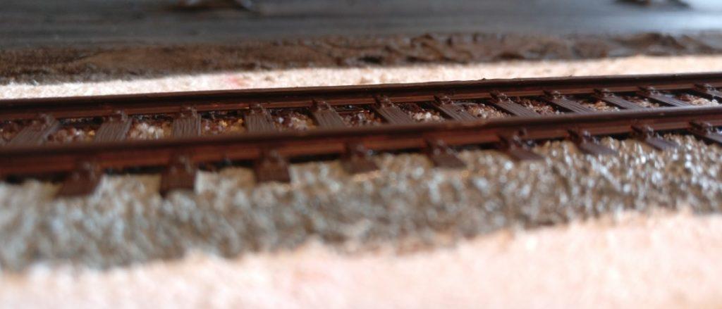 """Erste Arbeiten am Gleis: der Stahl wird mit wässriger """"Lederbraun"""" grundiert."""
