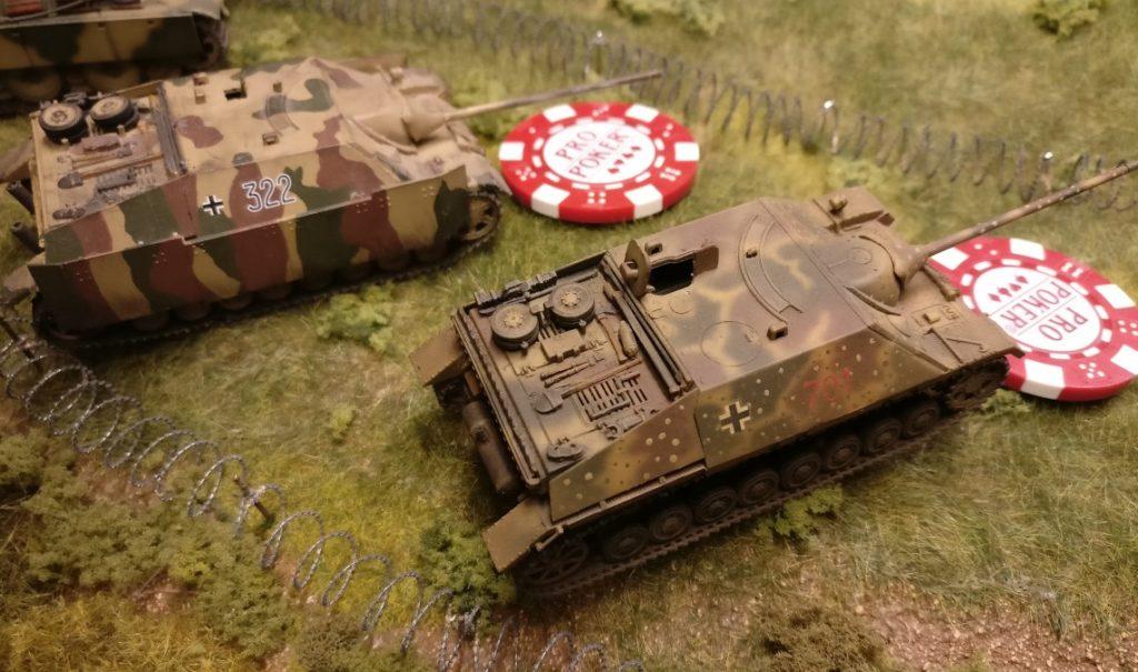 Diese beiden Jagdpanzer IV werden in Feuerbereitschaft versetzt. Zur Kennzeichnung der Feuerbereitschaft wird bei jedem der beiden Jagdpanzer IV ein roter Marker ausgelegt. So lauern Sie den anrückenden Sherman-Tanks auf. Vorteil der Feuerbereitschaft: Das Feuer konzentriert sich nur auf Feindfahrzeuge, welche den Wert ihrer Kommandokarte erwürfelt haben. Kein Schuss wird auf Fahrzeuge verschwendet, welche dann eventuell beim Aktivierungstest scheitern und den Wert ihrer Kommandokarte gar nicht erwürfeln.