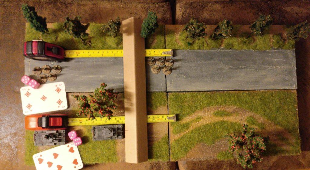 Auf diesem Bild versinnbildlicht der senkrecht abgebildete Pappwinkel der besseren Sichtbarkeit halber die Panzersperre. Der Infanterietrupp oben kann sich ungehindert durch die Panzerperren hindurch bewegen. Der Panzer 38(t) unten kann sich nur bis zur Panzersperre bewegen. Erst wenn die Panzersperre mit ihren drei Strukturpunkten zerstört ist, kann der Panzer 38(t) die Panzersperre überwinden.