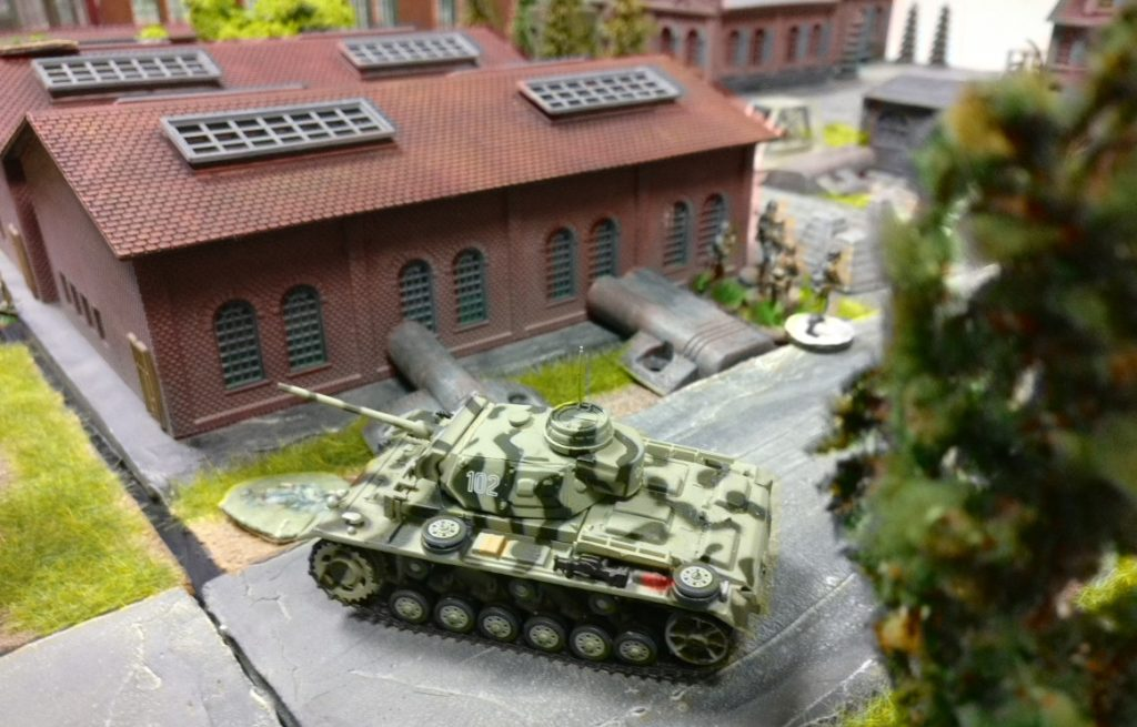 Ein Panzer III auf der Spielplatte Shturmigrad. Die einzeln basierten Minis deuten es an: Florian und Dominic wurden für einen Moment rückfällig und spielten eine Partie Behind Omaha nach den von Doncolor verbesserten Regeln. Sturmi war auch unter den Tätern, doch rächte sich die Verfehlung sehr schnell: Er verlor das Spiel...
