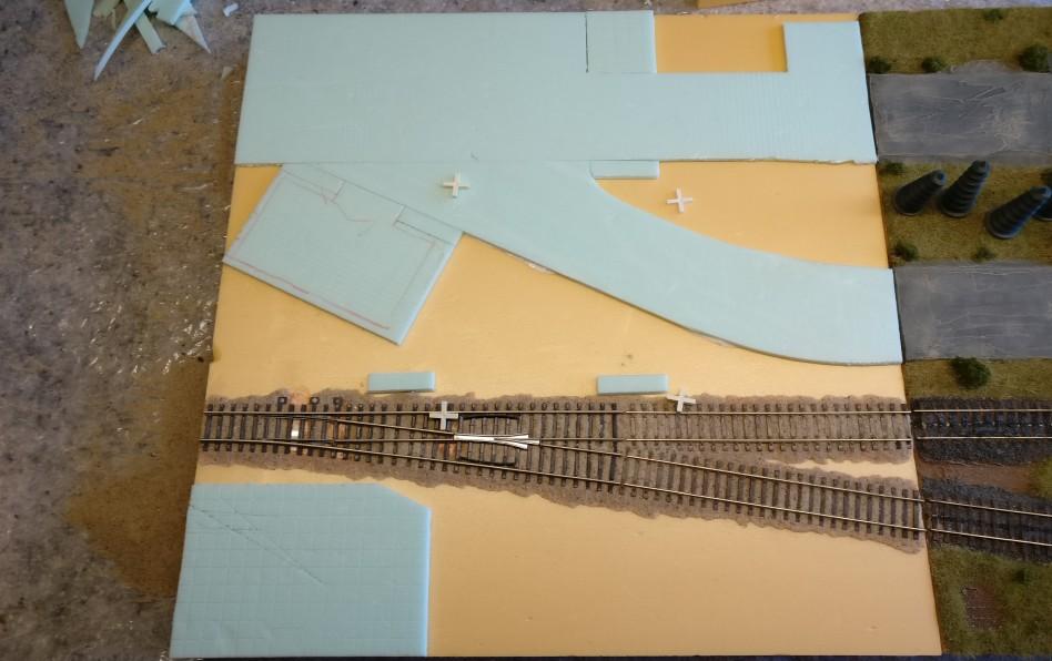 """Wie man sieht, wurden doch noch ein paar kleine Änderungen vorgenommen. Oben mittig wurde die Seitenfläche der Betonpiste zum Auffüllen auf das 15cm-PBI-Raster ergänzt. Auf der gegenüberliegenden Seite der Straße kam ebenfalls ein Fortsatz hinzu, um das 15cm-PBI-Raster zu bedienen. Oberhalb des geraden Geleises liegen zwei """"Betonstücke"""", die ebenfalls als Markierung für das PBI-Raster dienen. Und final habe ich die Lücken zwischen dem Fundament des kleinen Fabrikgebäudes und der betonpiste doch wieder verschlossen. Ich glaube, das hätte man im Original auch aus einem Stück betoniert und nichts ausgespart."""