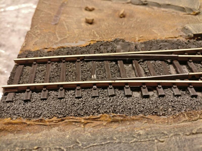 """Man erkennt sofort: erst jetzt nach dem Trockenbürsten mit """"Mittelgrau"""" ist der Kontrast zwischen den Schottersteinen und dem Dunkel des Schattens darunter hinreichend stark."""
