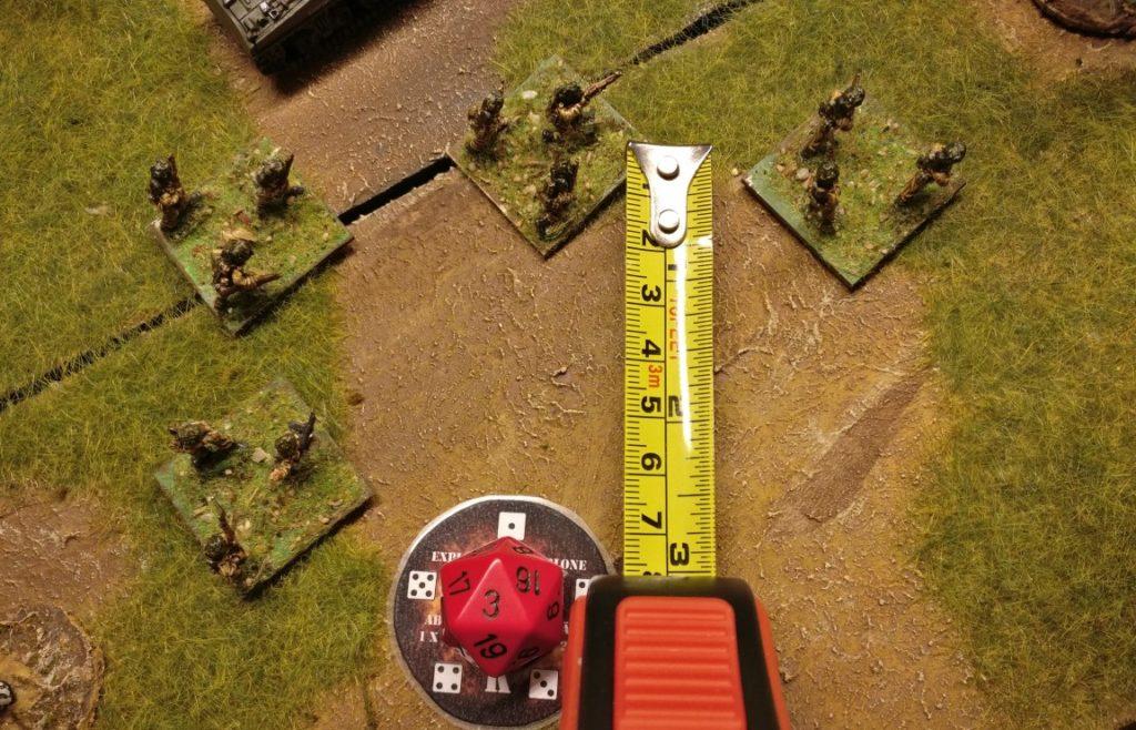 Mit dem Maßband tragen wir jetzt die erwürfelte Abweichungsdistanz von 3 Zoll in der erwürfelten Richtung ab. In unserem Beispiel wäre das ziemlich genau die Mitte der Infanterie-Base des Tommy-Trupps. Die Messung der Abweichungsdistanz beginnt in der Mitte der ursprünglich als Ziel ausgelegten Trefferschablone.