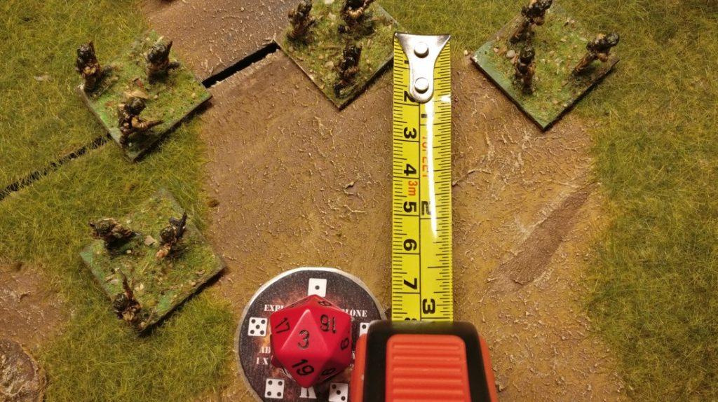 Bei der Ermittlung der Abweichung würfelt man mit dem Abweichungswürfel. Dies ist ein W8-, W12- oder W20-Würfel. Die gewürfelte Zahl gibt die Abweichung in Zoll an. Die Spitze der Fläche, auf welcher die Zahl aufgeprägt ist, zeigt an, in welche Richtung die Abweichung den Einschlag ablenkt. In unserem Beispiel hier sieht man, dass durch die Abweichung die Trefferschablone direkt auf einem der Infanterietrupps zu liegen kommen wird.