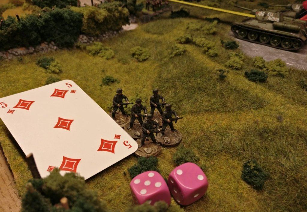 """Diese Infanterieeinheit muss gemäß der ausliegenden roten Karte mindestens eine """"5"""" würfeln. Mit den beiden zur Verfügung stehenden Würfeln ist dies gerade noch gelungen. Die Einheit bleibt in ihrer Stellung."""