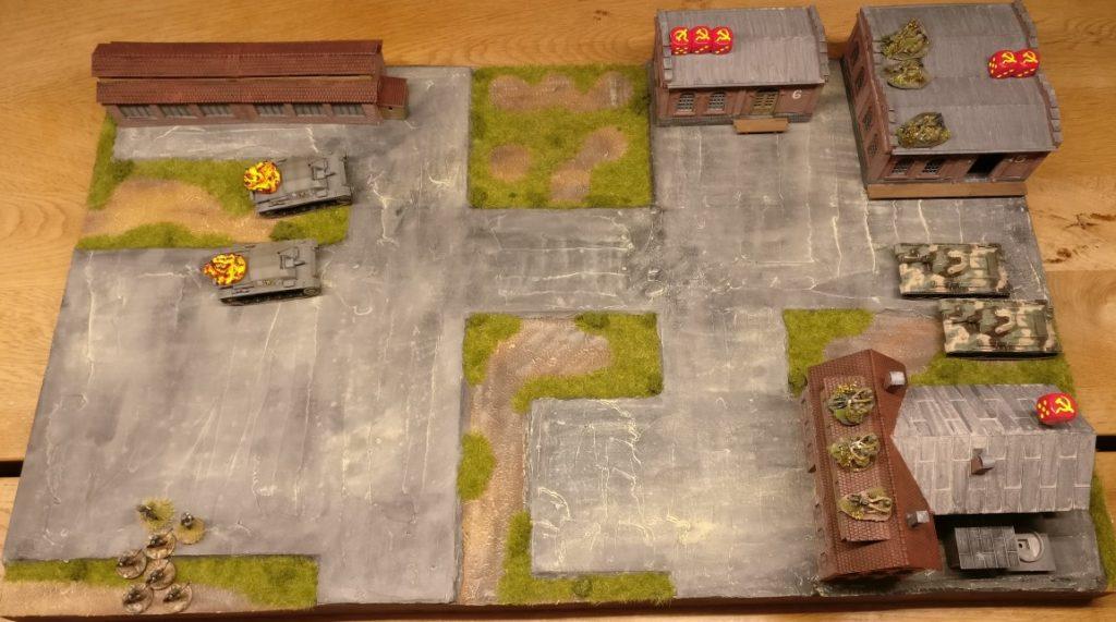 Hier befinden wir uns gerade in Shturmigrad, das aufs Heftigste von der Roten Armee verteidigt wird. In der rechten Hälfte des Spielfeldes sieht man drei durch rote Sichelwürfel gekennzeichnete Schlüsselpositionen. Linker Hand erkennt man zwei deutsche Kampfgruppen, die sich der Schlüsselpositionen annehmen.
