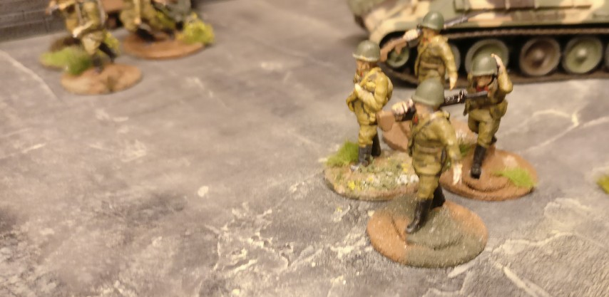 Ein Infanterietrupp sprintet vor zwei T-34/76 nach vorne.