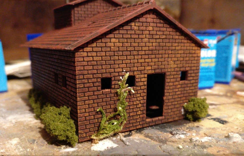 An der Vorderseite des 6017 Vollmer H0 Kamin für Kesselhaus rankt ein Trieb zwischen den Fenstern nach oben.