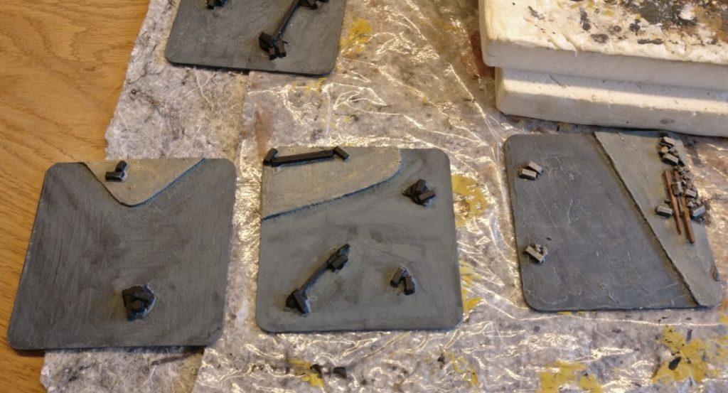 Hier sind die Blaugrau und die Beige des Gehsteigs aufgetragen. Holzbalken und Mauerstücke tragen noch die schwarze Grundfarbe.