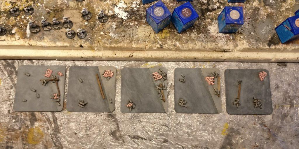 Einige Basen aus Bierdeckel mit Sandstein-Mauerstücken.