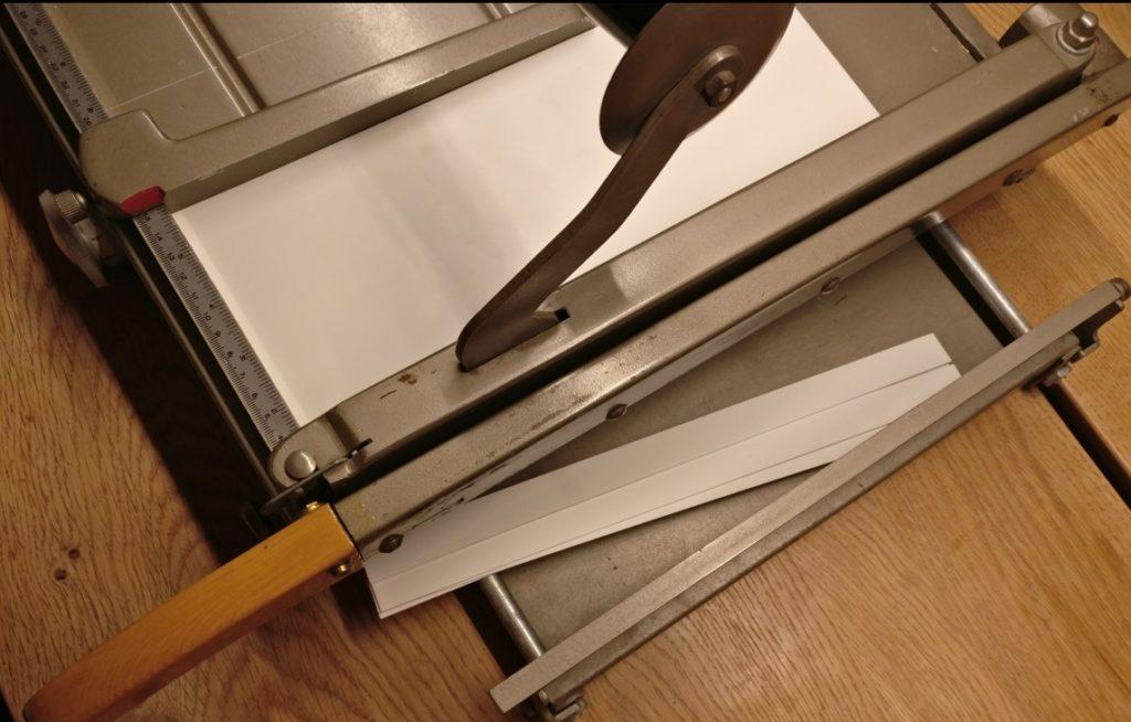 Mittels der Papierschneidemaschine schneide ich Streifen mit exakter Breite vom Plastic Sheet ab.