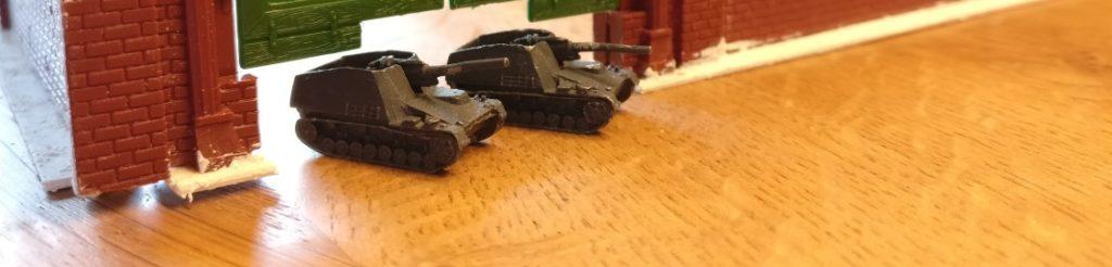 """Unter den Flügeln der Hallentore des """"Vollmer 5752 H0 Lokschuppen 2-ständig"""" können ganze Panzer durchfahren, so wie hier die """"Hummel"""", die 15 cm schwere Panzerhaubitze 18/1 auf Fahrgestell Panzerkampfwagen III/IV (Sf) (Sd.Kfz. 165) - hier als 6mm/1:285 Modelle von GHQ."""