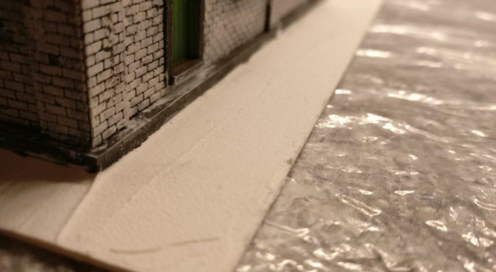 Die Sockelplatte des Maschinenleitstandes wird mit Innenspachtel bestrichen.
