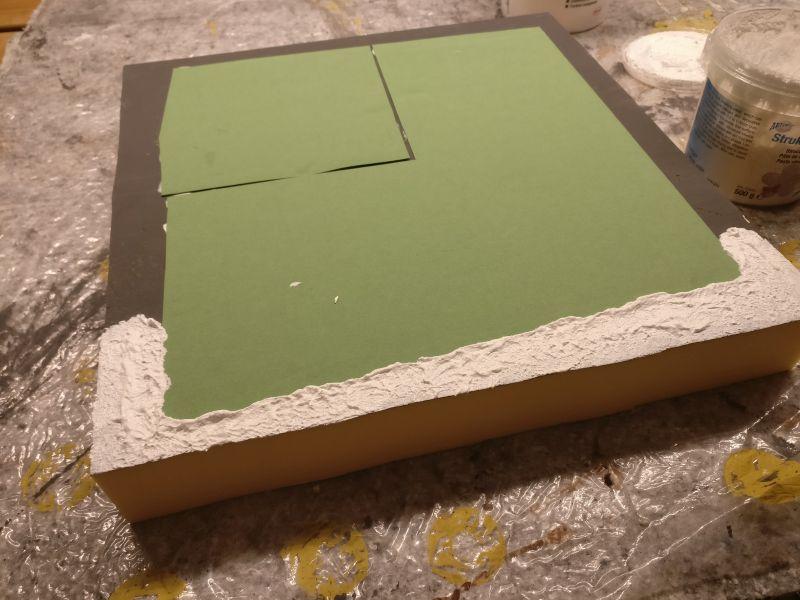 Hier der Karton auf die beiden angekündigten Reisfeldgrößen zurecht geschnitten. Vorne wird bereits Strukturpaste als umgebendes Erdreich aufgetragen. Die Strukturpaste nehme ich gerne als Darsteller für Erdreich jeglicher Art. Sie ergibt später getreu ihres Namens eine hervorragend unruhige Oberflächenstruktur.