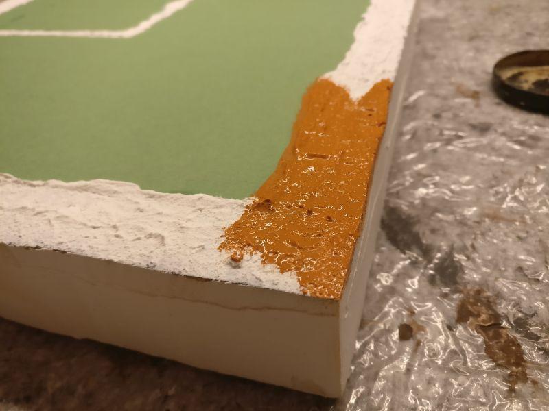 Die Grundfarbe Revell Aquacolor Braun wird auf alle Partien Erdreich aufgetragen.