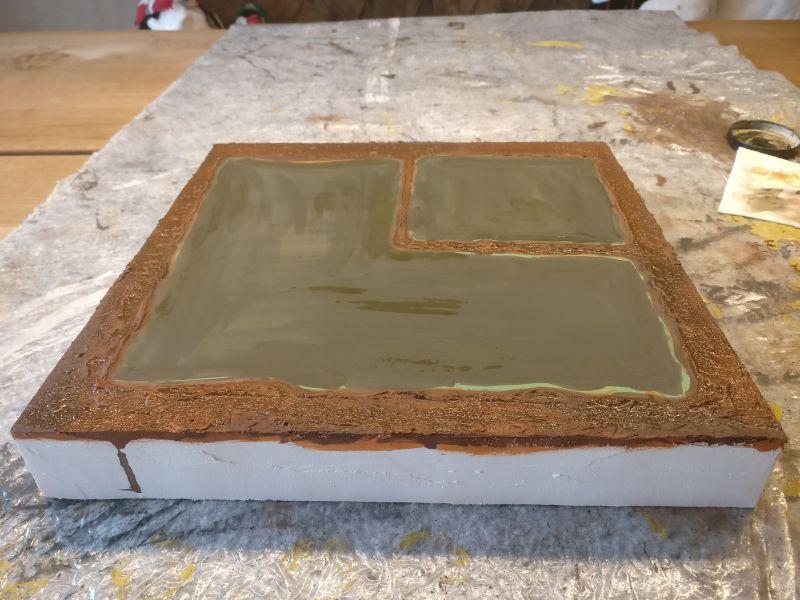 """Der Karton als Wasseroberfläche wurde mit Gelboliv behandelt. Die """"Uferpartie"""" wurde noch ausgespart. Sie wird nochmals separat behandelt."""