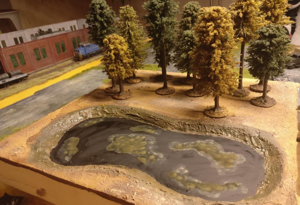 Hier ist die Böschung des sumpfigen Sees mit Grün behandelt. Auf der Wasseroberfläche sind bereits verschiedene Lasuren zum Einsatz gekommen. Von Erdbraun über Grüngrau bis hin zu Gelboliv.