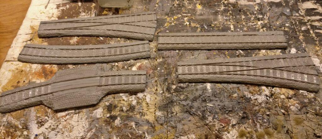 Die Grundierung der Schienenstücke aus Resin ist bereits erfolgt: Der Auftrag der Revell Aquacolor Mittelgrau gibt nicht nur eine stabile Grundierung ab, sondern wird später dem Schotter die Farbe verleihen.