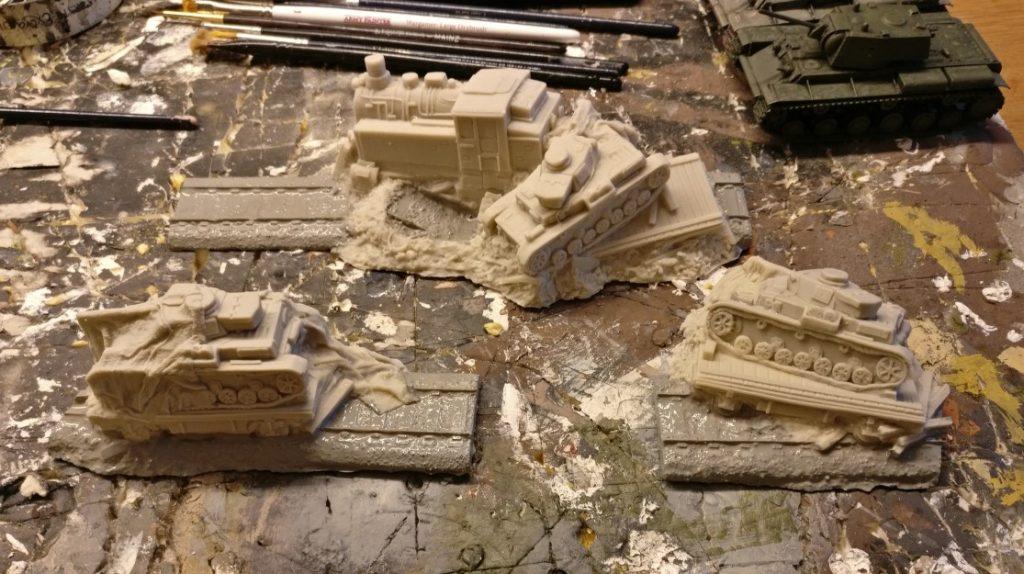 Auch die kurzen Schienenstücke aus Resin mit den umgestürzten Schwerlasttransportern werden grundiert. Allerdings grundiere ich nur den Gleiskörper. Die Eisenbahnwaggons und die Panzerkampfwagen IV bleiben unbehandelt.