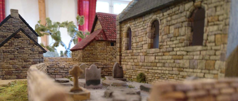 """Der alte Friedhof mit seinen spitz zulaufenden Mauern hinter der Kapelle in Cauquigny auf der Spielplatte """"Die Brücke von La Fière"""""""