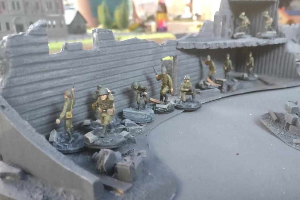 Hinter der Häuserwand geht ein weiterer Infanteriezug vor, bereit zum Sturm.