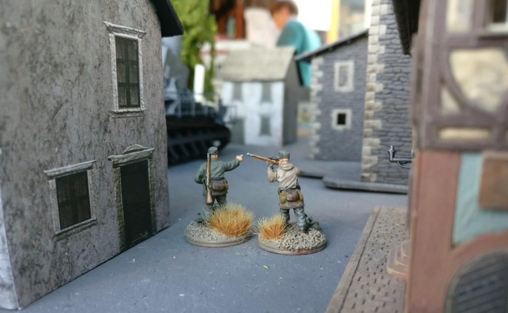 """Zwei Veteranen marschieren zum 60cm Mörser """"Eva"""", den man im Hintergrund auf dem Marktplatz erkennt."""