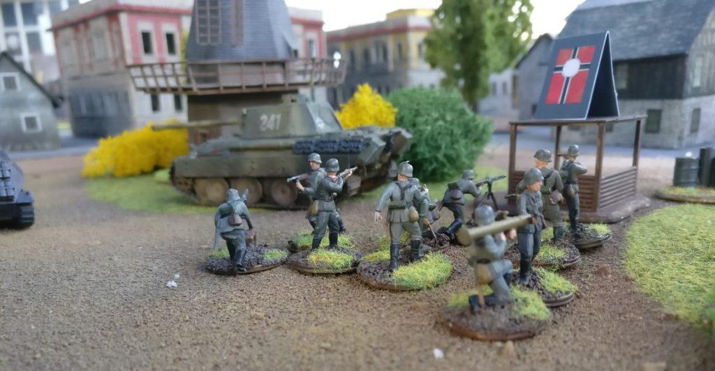 Ein deutscher Trupp Panzergrenadiere nahe dem Panther an der Windmühle.
