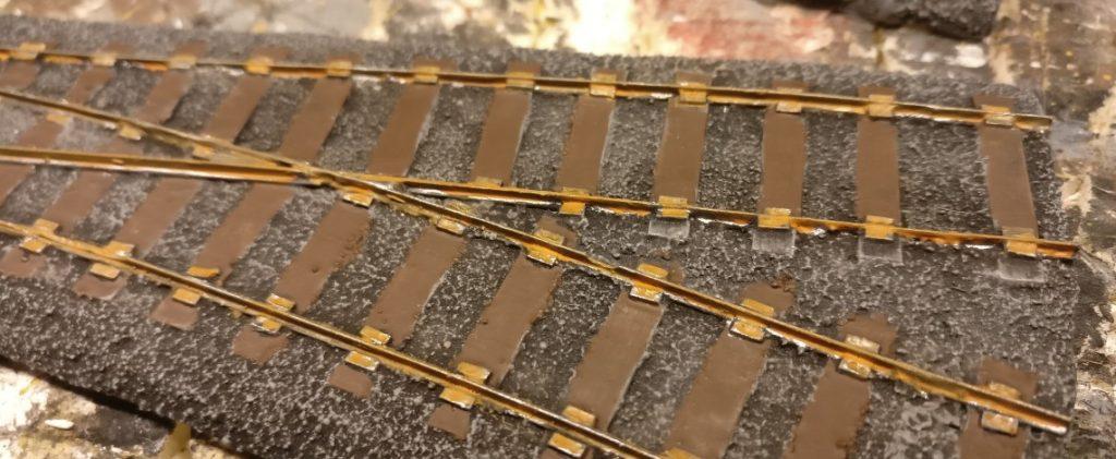 """Nach dem Trocknen des recht rötlichen Farbtons Revell Aquacolor 36185 Braun nehmen die Schienen schon Gestalt an. Das zu kräftige Blitzen des mit Gunmetal erzeugten metallischen Eindrucks ist gebrochen und wirkt jetzt schon wesentlich """"schieniger""""."""