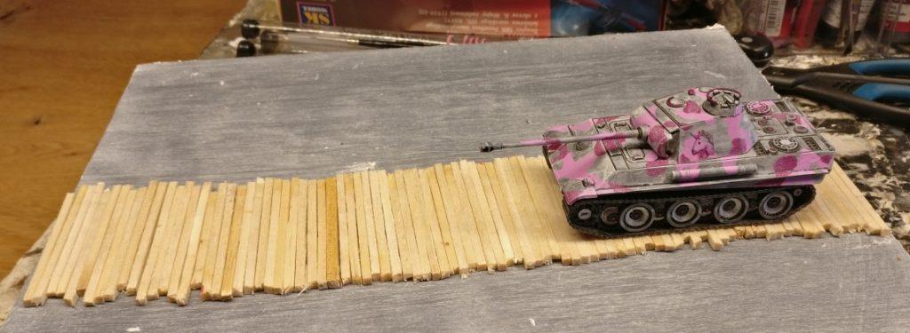 Die klein geschnittenen Streichhölzer sind hier zur Probe aufgelegt. Der aufgesetzte Panther  zeigt, das der Knüppeldamm ausreichend breit sein wird.