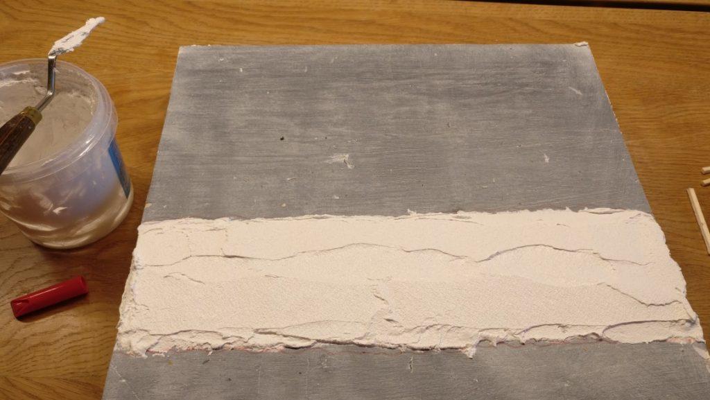 Die Strukturpaste wird im markierten Areal aufgebracht und glatt verstrichen. Die Schicht ist etwa 3mm hoch.
